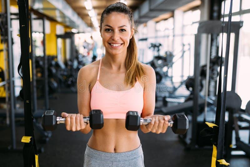 Jeune femme sportive faisant une séance d'entraînement de forme physique avec des haltères images libres de droits