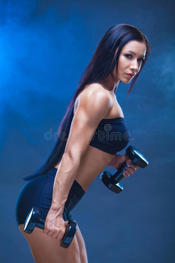 Jeune femme sportive faisant une séance d'entraînement de forme physique avec des haltères sur le fond noir de studio Autour des  photographie stock libre de droits