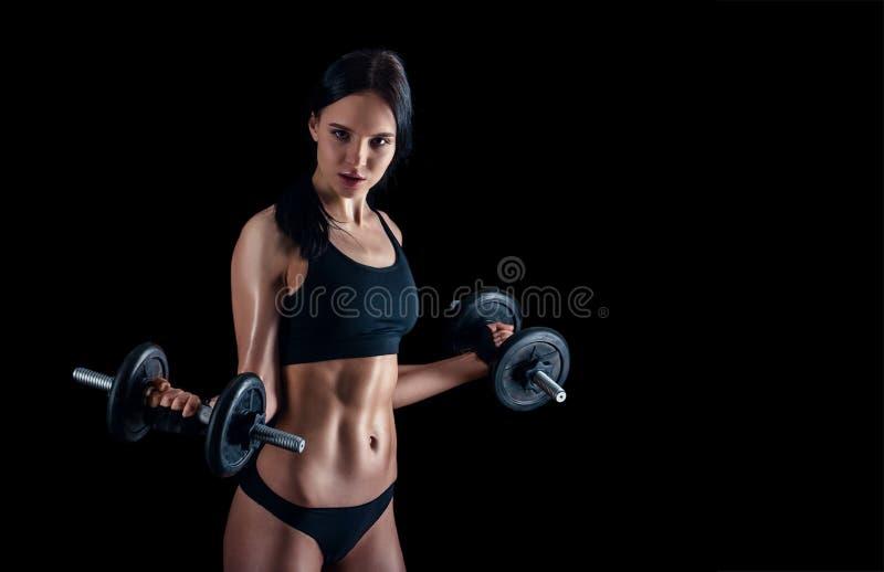 Jeune femme sportive faisant une séance d'entraînement de forme physique sur le fond noir La fille attirante de forme physique po photographie stock libre de droits