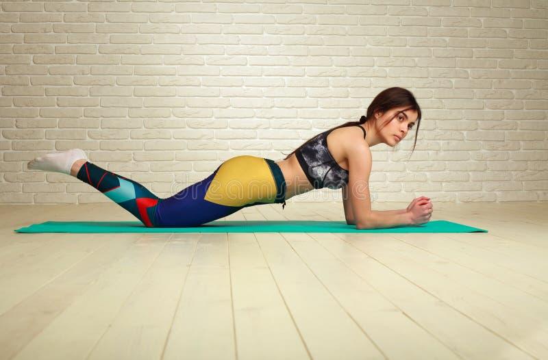 Jeune femme sportive mince faisant la forme physique ?tirant des exercices et la s?ance d'entra?nement de pompes dans le mode de  photos libres de droits