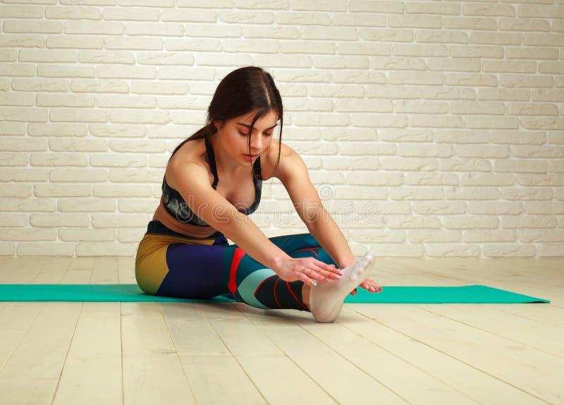 Jeune femme sportive mince faisant la forme physique ?tirant des exercices et la s?ance d'entra?nement de pompes dans le mode de  photographie stock libre de droits