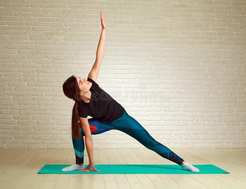 Jeune femme sportive mince faisant la forme physique ?tirant des exercices et la s?ance d'entra?nement de pompes dans le mode de  photo libre de droits