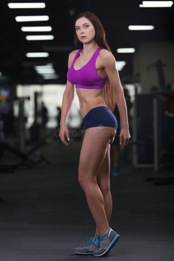 Jeune femme sportive montrant des muscles après séance d'entraînement dans le gymnase photos stock