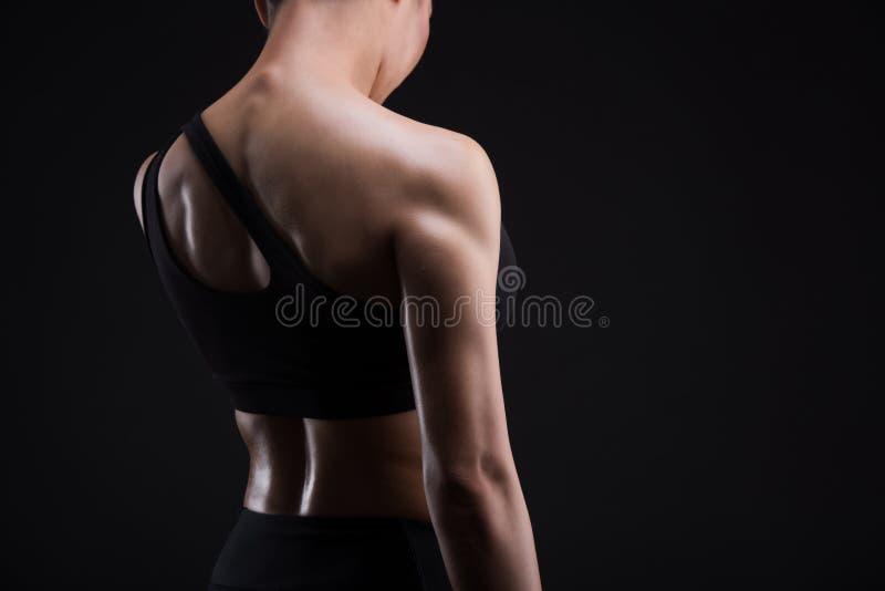Jeune femme sportive montrant des muscles du dos photos stock