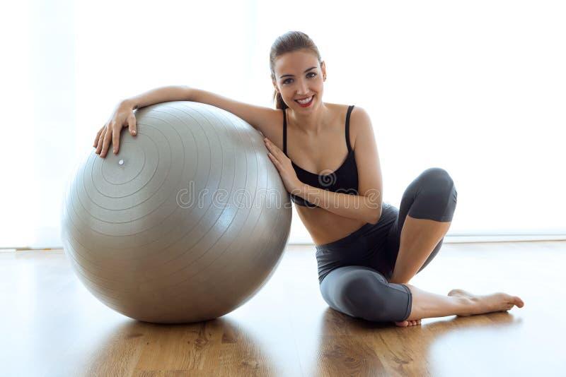 Jeune femme sportive posant avec la boule et regardant l'appareil-photo à la maison image libre de droits