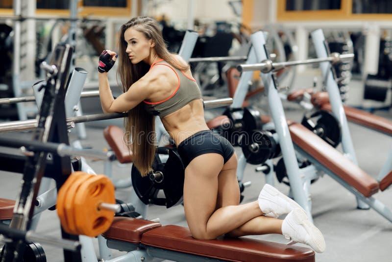 Jeune femme sportive posant sur le banc à presse image stock