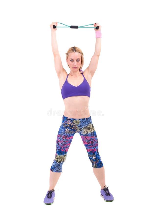 Jeune femme sportive s'exerçant avec une corde de résistance images stock