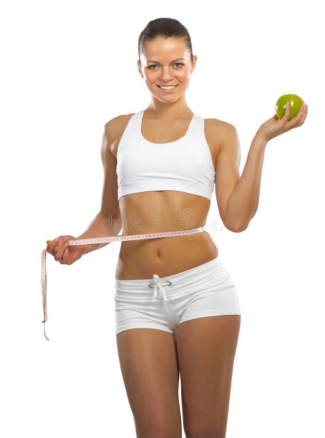 Jeune femme sportive tenant une pomme verte image libre de droits
