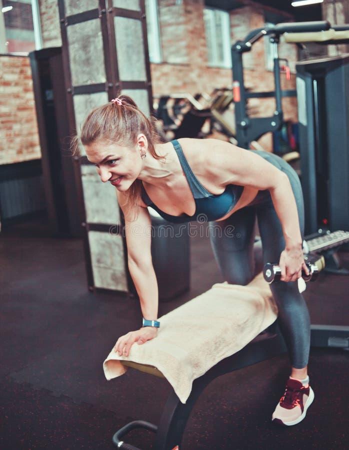 Jeune femme sportive tirant l'haltère images stock