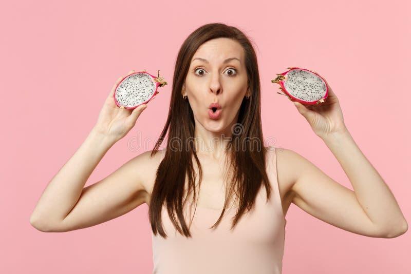 Jeune femme stupéfaite tenant dans des mains deux halfs de pitahaya mûr frais, fruit du dragon d'isolement sur le mur en pastel r image stock