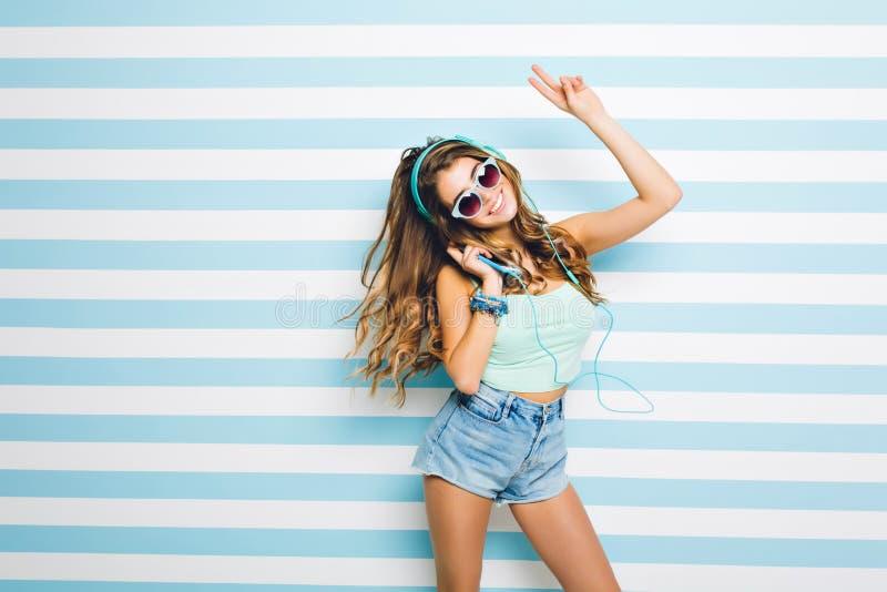 Jeune femme stupéfiante portant au dessus du réservoir élégant et lunettes de soleil ayant l'amusement à la maison, chanson préfé image stock