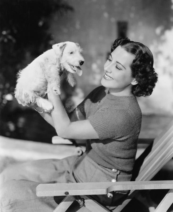 Jeune femme supportant son chiot et sourire (toutes les personnes représentées ne sont pas plus long vivantes et aucun domaine n' image stock