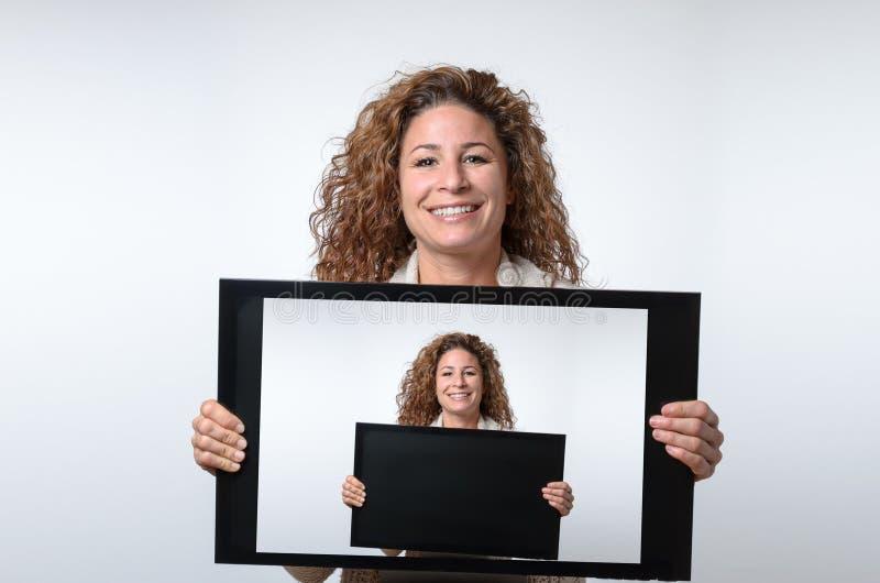 Jeune femme supportant un moniteur vide photos stock