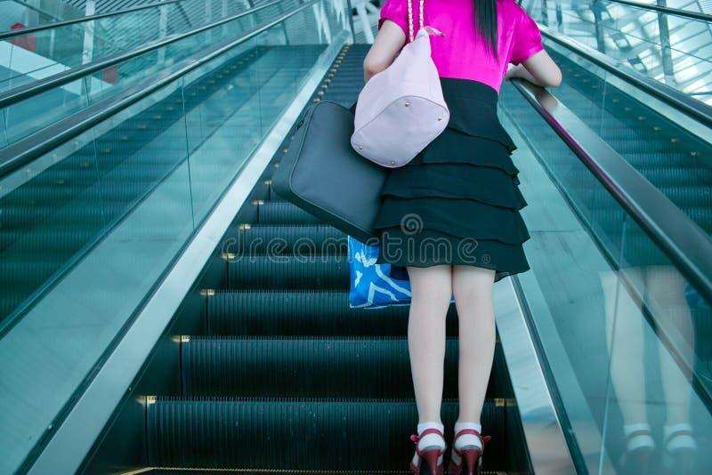 Jeune femme sur l'escalator photo stock