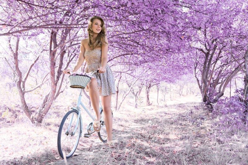 Jeune femme sur la bicyclette dans la forêt de rose d'imagination photos stock