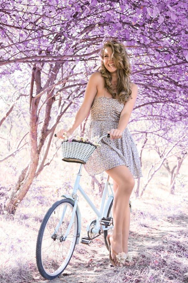 Jeune femme sur la bicyclette dans la forêt de rose d'imagination images stock