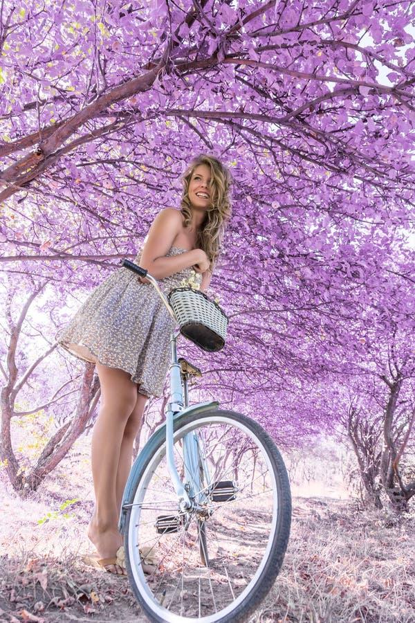 Jeune femme sur la bicyclette dans la forêt de rose d'imagination photo libre de droits