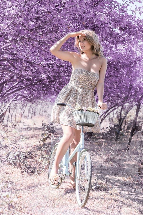 Jeune femme sur la bicyclette dans la forêt de rose d'imagination photos libres de droits