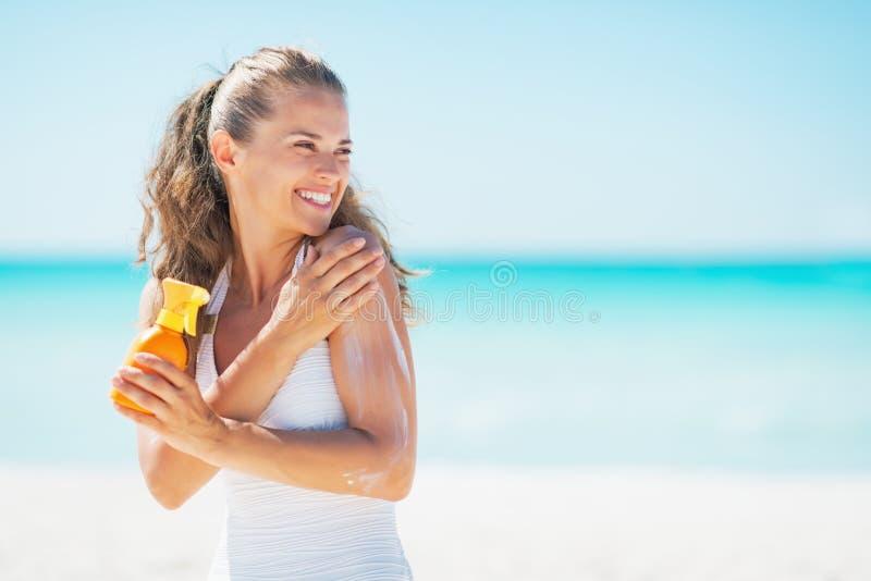 Jeune femme sur la plage appliquant la crème de bloc du soleil image libre de droits