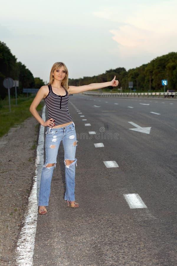 Jeune femme sur le bord de la route photo stock