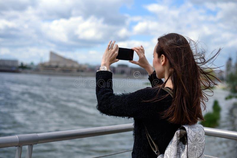 Jeune femme sur le bord de mer prenant des photos du paysage de ville photographie stock libre de droits