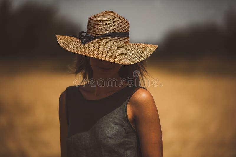 Jeune femme sur le champ cachant ses yeux au-dessous de son chapeau images libres de droits