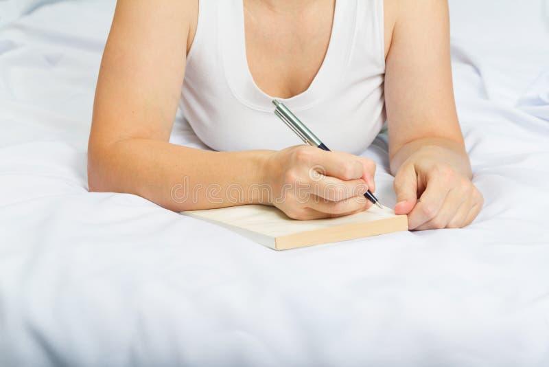 Jeune femme sur le lit avec le carnet images stock
