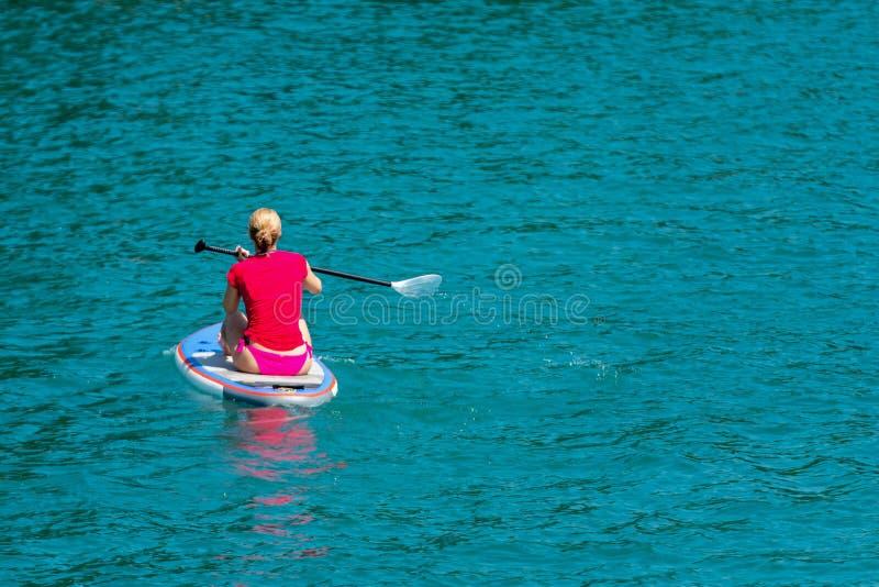 Jeune femme sur le panneau de palette au lac sup Vue de dos photo stock