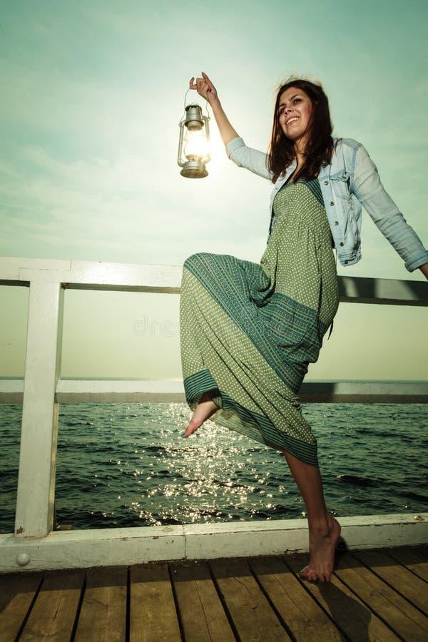 Jeune femme sur le pilier avec la lampe de kérosène d'huile photographie stock libre de droits