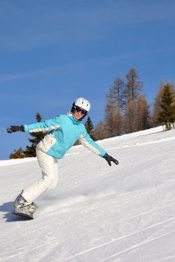 Jeune femme sur le snowboard images stock