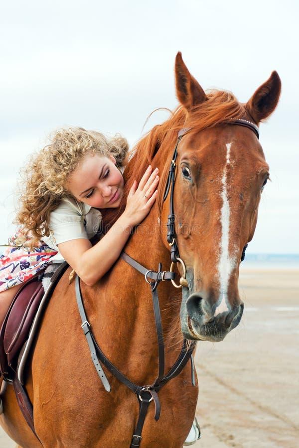 Jeune femme sur un cheval photo stock