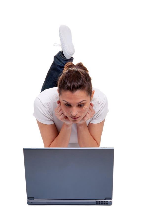 Jeune femme sur un ordinateur portable photos stock