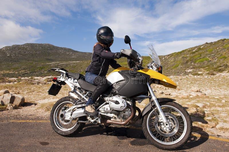 Jeune femme sur un vélo jaune photos stock