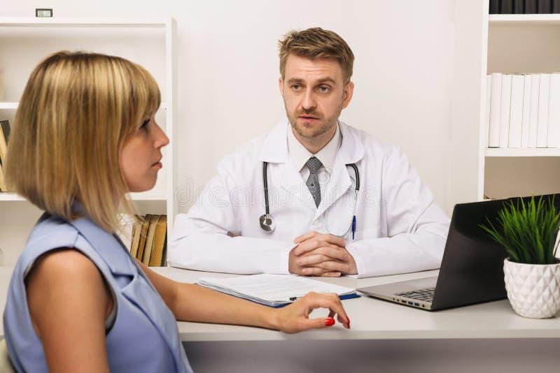 Jeune femme sur une consultation avec un chirurgien ou un thérapeute masculin dans son bureau photo stock