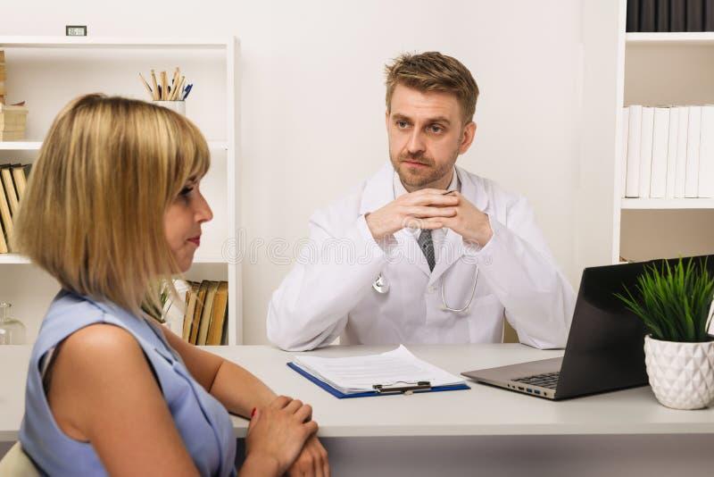 Jeune femme sur une consultation avec un chirurgien ou un thérapeute masculin dans son bureau photos stock
