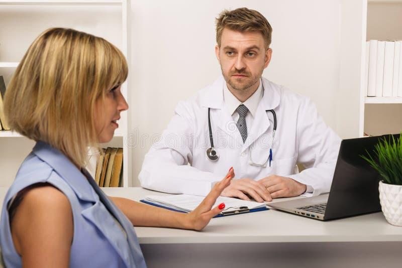 Jeune femme sur une consultation avec un chirurgien ou un thérapeute masculin dans son bureau photographie stock libre de droits