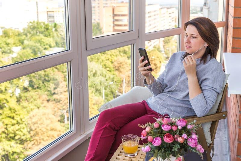 Jeune femme sur une musique de écoute de balcon ou parler par le téléphone images libres de droits