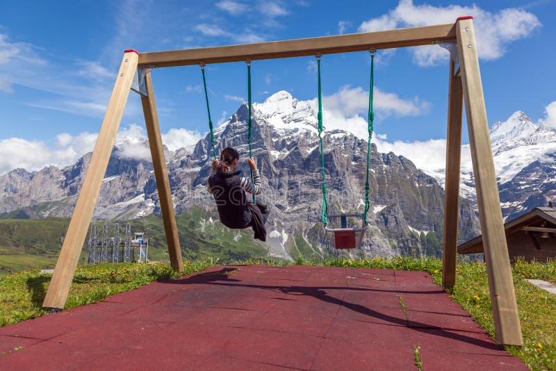 Jeune femme sur une oscillation, balançant au-dessus des montagnes, Grindelwald image libre de droits