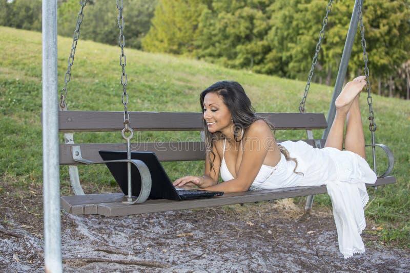 Jeune femme sur une oscillation, utilisant un ordinateur portable photographie stock libre de droits