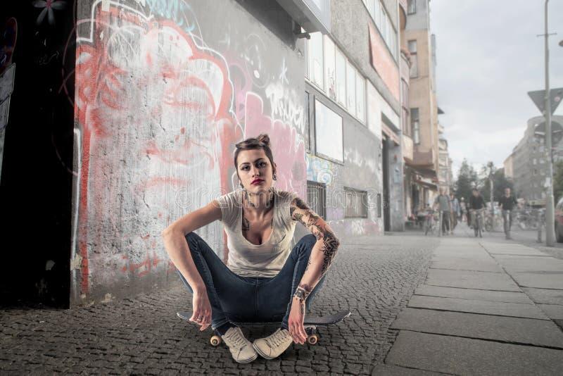 Jeune femme sur une planche à roulettes photographie stock