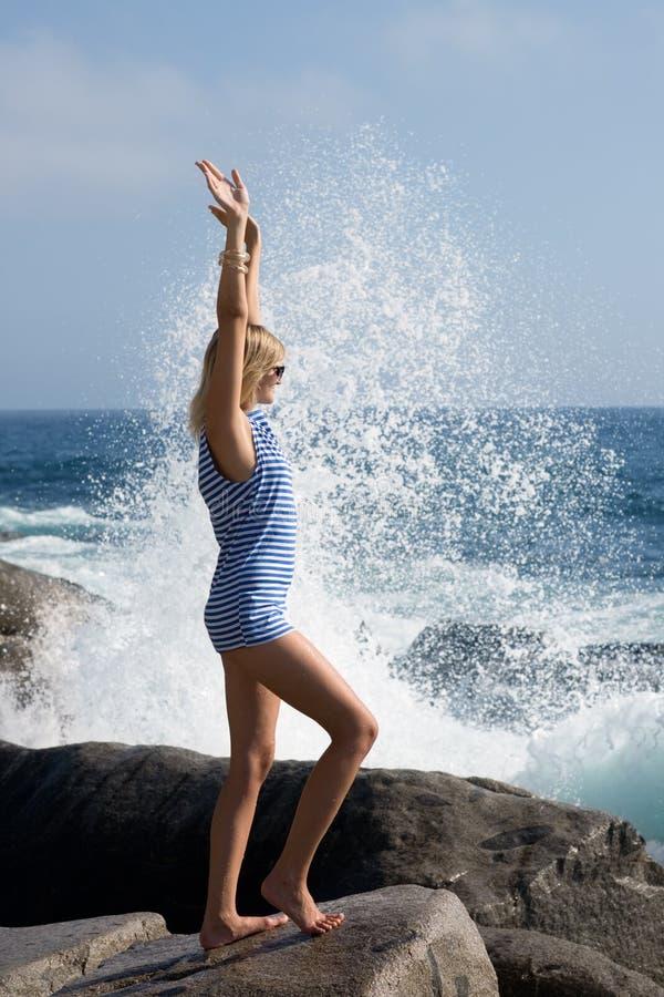 Jeune femme sur une roche contre l'éclaboussure de mer image libre de droits