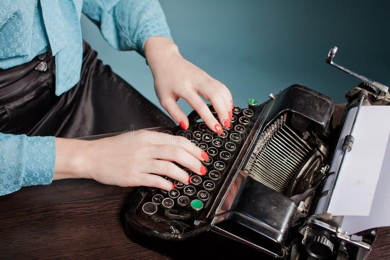 Jeune femme tapant avec la vieille machine à écrire photos stock