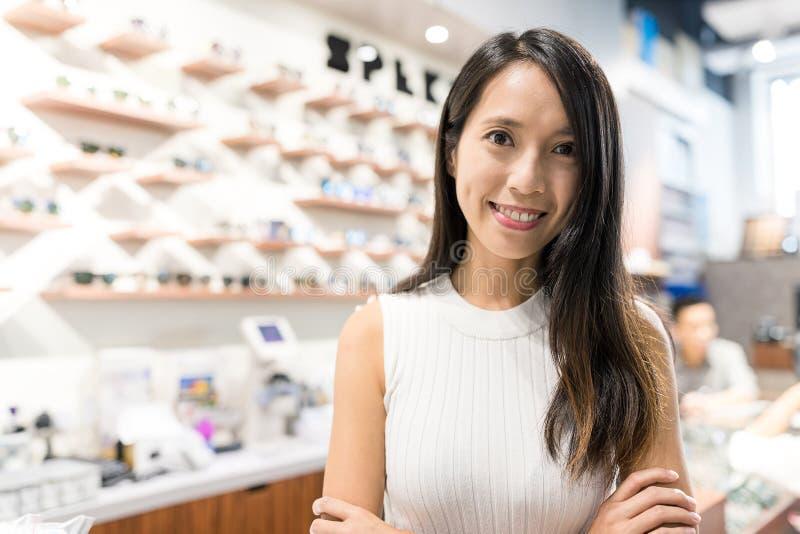 Jeune femme tenant des affaires dans la boutique d'opticien photographie stock