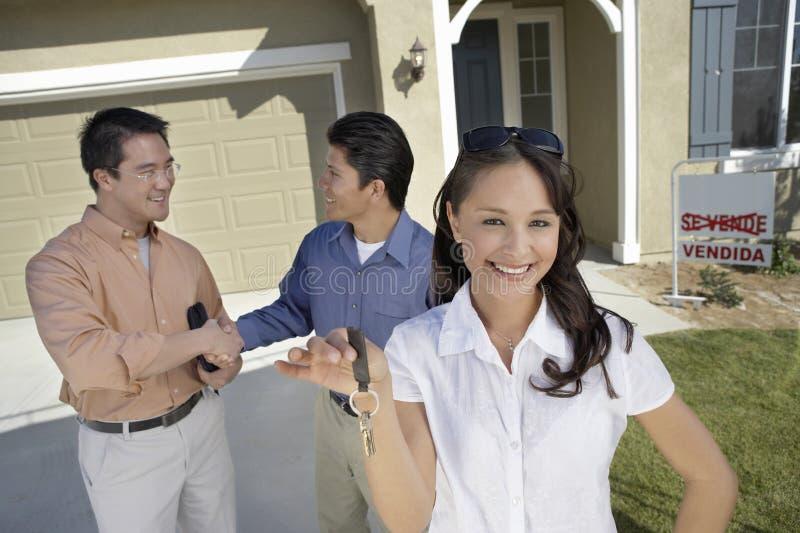 Jeune femme tenant des clés de nouvelle maison image stock