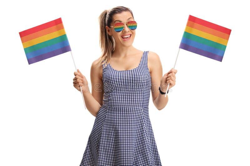 Jeune femme tenant des drapeaux d'arc-en-ciel photo stock