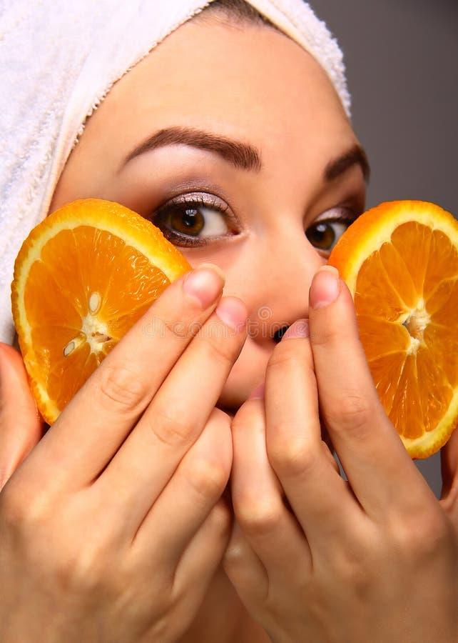 Jeune femme tenant des morceaux d'orange images stock