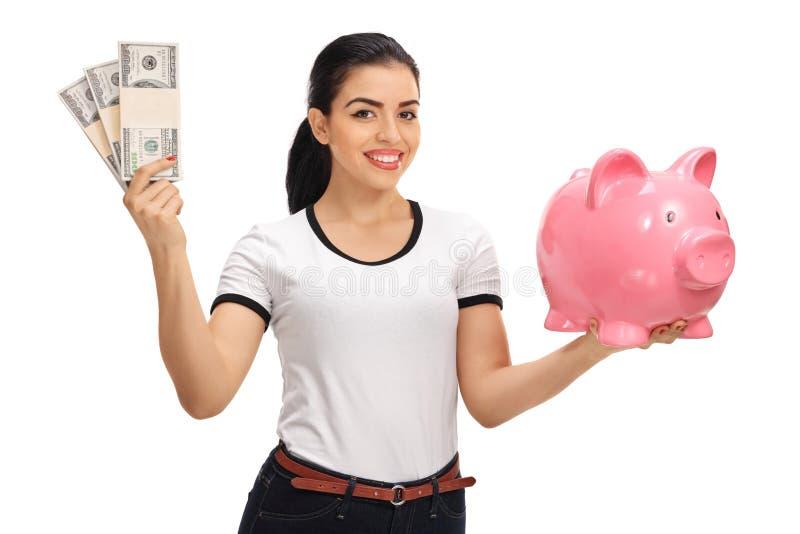 Jeune femme tenant des paquets d'argent et de tirelire photographie stock libre de droits