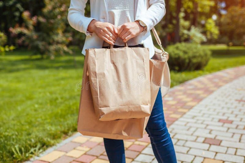 Jeune femme tenant des sacs en papier d'achats en parc d'?t? et utilisant l'?quipement ? la mode photo stock