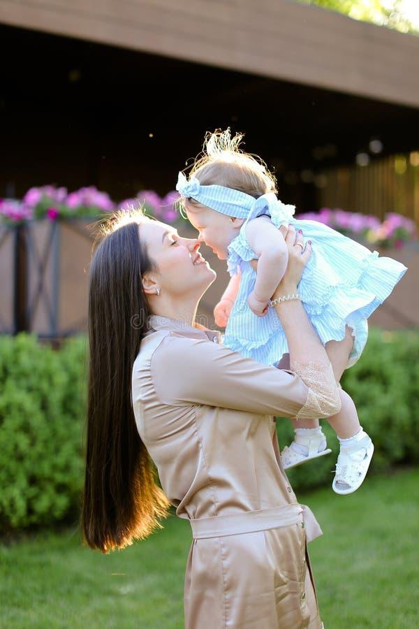 Jeune femme tenant et embrassant peu de fille photos stock