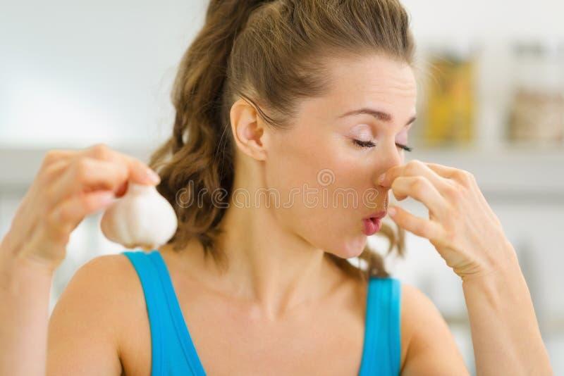 Jeune femme tenant l'ail puant image stock